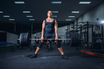 Powerlifter keeps the weight of heavy barbell