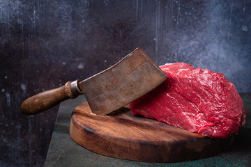 Raw beef and meat cleaver on cutting board on grunge background