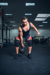 Man in sportswear doing exercise with kettlebell