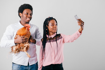 Loving interracial couple with cock in hand isolated on white background take selfie with smartphone. Happy dark skinned man with his young dark skinned girllfriend and rooster in hand studio portrait