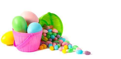 Easter eggs and candy in colorful baskets on white background, copy space