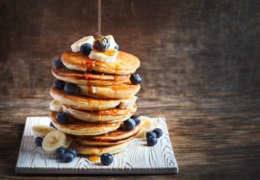 Pancakes with banana, blueberry and maple syrup for a breakfast