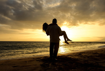 silhouette of couple on the beach at sunset