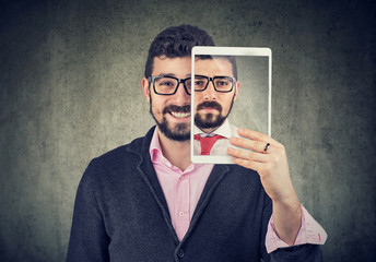 Cheerful man holding a tablet with serious self portrait on screen
