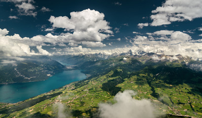 Aerial shot of Bernese Alps, lush valley and Lake Thun, Berner Oberland, Switzerland.