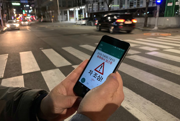 Kim Jong-hoon, a senior researcher at Korea Institute of Civil Engineering and Building Technology (KICT) demonstrates an application 'Watch Out' that gives an alert to a user distracted by using smart phone while crossing a zebra crossing, in Ilsan