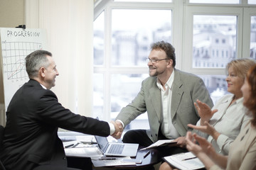 handshake business partners after discussion of the contract.
