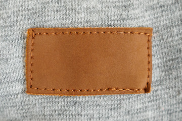 Blank brown leather cloth label on gray fabric textile background