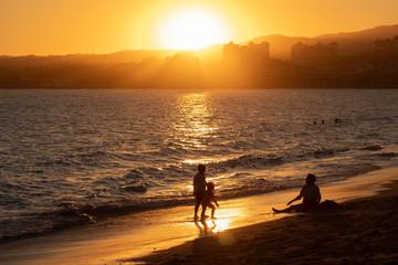Una madre y sus hijos jugando en la playa, durante el atardecer, Bucerias, Riviera Nayarit, Mexico.
