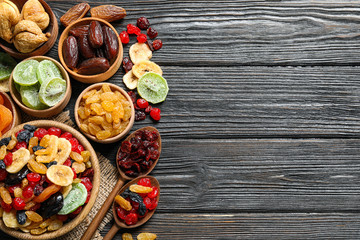 Flat lay composition with different dried fruits on wooden background. Space for text