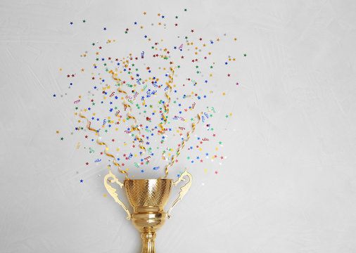 Trophy and confetti on light background, top view with space for text. Victory concept