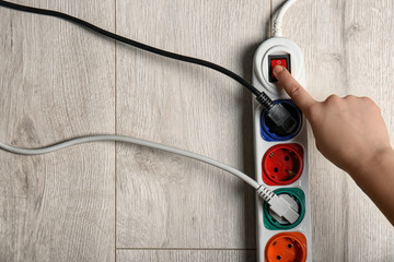 Woman pressing power button of extension cord on wooden floor, top view with space for text. Electrician's equipment