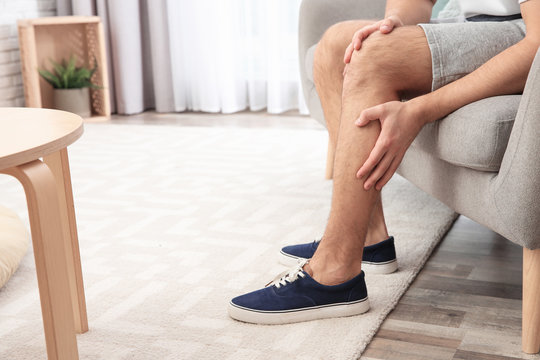 Man suffering from leg pain at home, closeup. Space for text