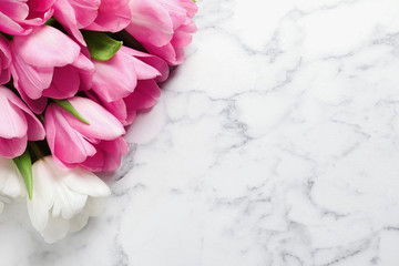 Beautiful tulips on marble background, top view with space for text. International Women's Day