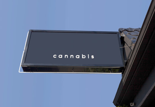 Legal cannabis store sign with copy space against blue sky.