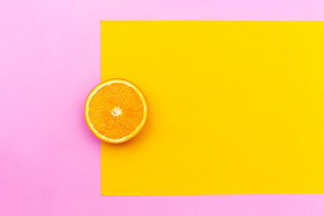 One circle slice of fresh ripe orange with pulp and peel on yellow and pink background. Top view. Clipping path - image