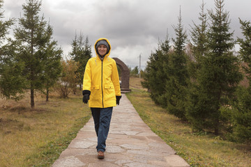 young woman in raincoat walks in park in cloudy weather, copy space