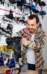 Male repairer fixing roller-skates in sports store