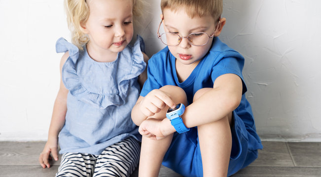 A little boy child in a blue T-shirt and glasses shows the girl his smart watch and presses a finger.