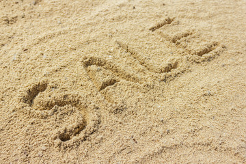 Sale word written on the sand at the beach, natural background