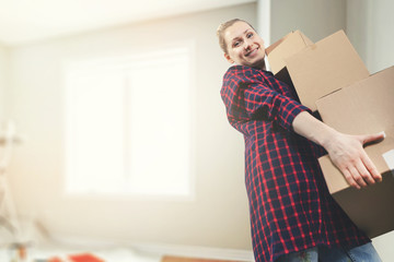 moving into a new house - smiling young woman carrying boxes. copy space