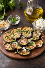 Fried eggplant with feta, pine nuts, fresh herbs (cilantro, parsley) and olive oil. Tasty vegetable snack, summer, spring food, picnic