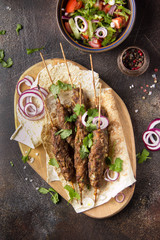 Lula kebab from minced meat (beef, lamb, veal) on pita bread (lavash), shish kebab. With red onion, cilantro and vegetable salad