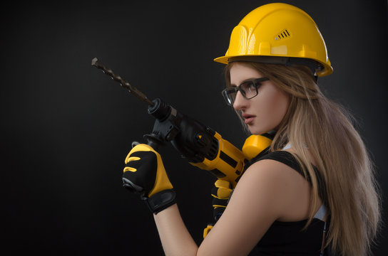 girl in construction clothes and protective equipment posing with a hammer