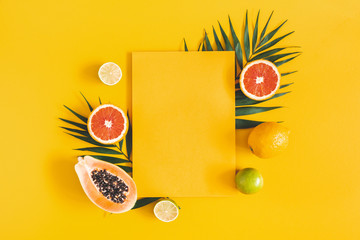 Summer composition. Tropical palm leaves, fruits, yellow paper blank on yellow background. Summer concept. Flat lay, top view, copy space