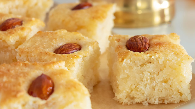 Close up pieces Basbousa or namoora traditional arabic semolina cake with almond nut and rose syrup. Selective focus.
