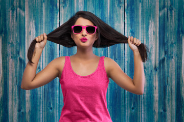 Portrait of young girl in pink top and fancy eye glasses holding her hair to her sides