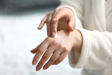 Young woman applying hand cream, closeup