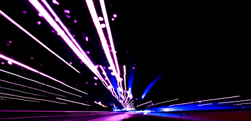 Cars light trails on a curved highway at night. Night traffic trails. Motion blur. Night city road with traffic headlight motion. Cityscape. Light up road by vehicle motion blur. Fotomurales