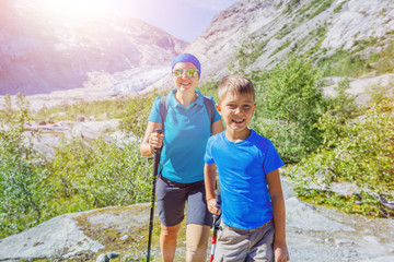 Best Norway hike. Cute boy and his mother with hiking equipment in the mountains