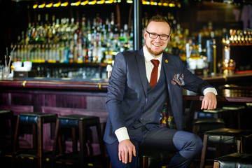 Businessman in good mood sitting in a bar after work