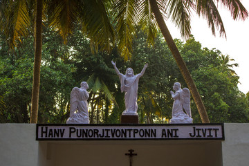 white statue of Jesus with two angels on a background of green palm trees