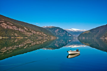 Beautiful Nature Norway natural landscape with fjord, boat and mountain.