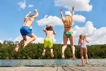 Glückliche Familie springt in einen See
