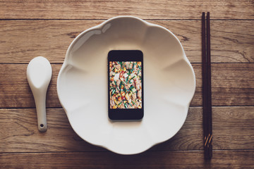 Mobile phone with food picture on screen in a plate on wooden table with chopsticks and spoon.
