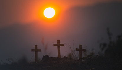 three wooden cross of christian standing with light sunset background. christian silhouette concept