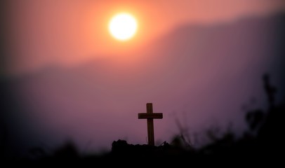 The cross standing with light sunset background. christian silhouette concept