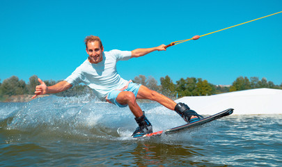 PORTRAIT: Cheerful wakeboarder gives the shaka sign while speeding past camera. Wall mural