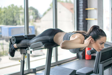 force physique Sports young woman doing exercises on trainer back machine in the gym