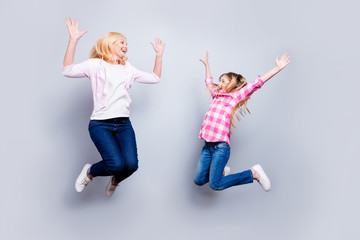 Full length body size photo two blond haired she her granny grandma little granddaughter jump high achievement wear jeans pink plaid checkered shirt sweater pullover isolated light grey background