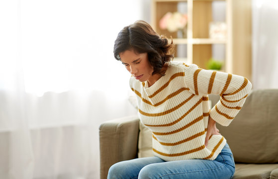 people, healthcare and problem concept - unhappy woman suffering from pain in back or reins at home