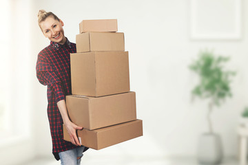 happy woman standing in new house with belonging boxes in hands