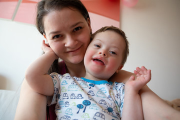Selfie of cute small boy with Down syndrome with his mother
