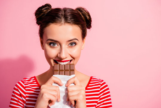 Close-up portrait of her she nice-looking cute charming attractive lovely glamorous cheerful girl in striped t-shirt biting tasting eating desirable favorite cocoa dessert isolated on pink background