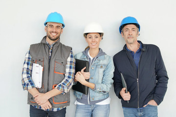 Mixed construction team smiling at camera on grey background