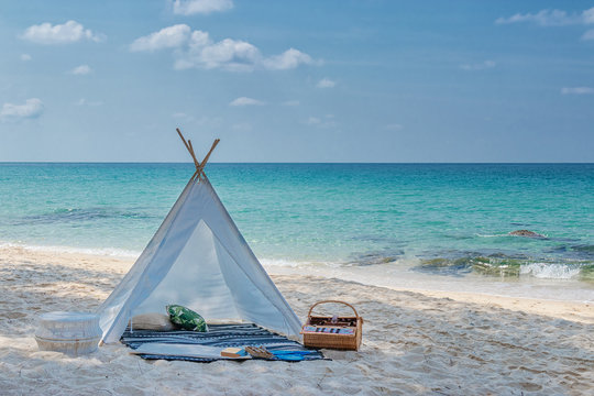 romantic white picnic tent on white sand beach with crystal clear water and blue sky at background